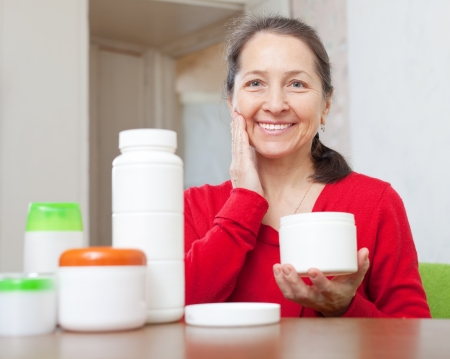 Smiling mature woman uses cosmetic cream in home interior photo