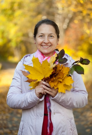 Happy mature woman  in jacket outdoors in autumn photo