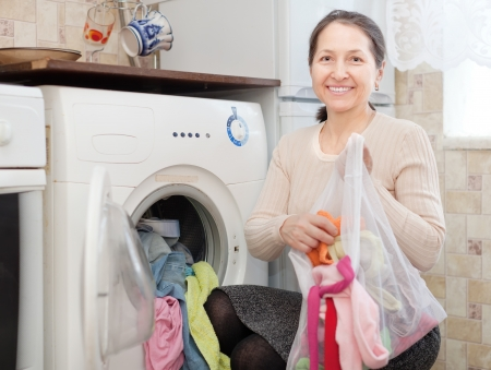 mature woman loading the washing machine with laundry bag Stock Photo - 22074525