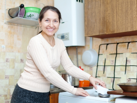 Happy mature woman cleans the gas-stove  with sponge  in kitchen at home photo
