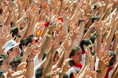 PAMPLONA, SPAIN - JULY 6: Start of San Fermin festival in July 6, 2013 in Pamplona, Spain. People raise their hands as a sign of beginning of  festival at ayuntamiento square