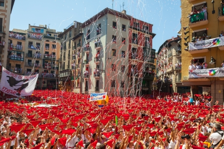 navarra: PAMPLONA, SPAIN - JULY 6: Start of San Fermin Festival in July 6, 2013 in Pamplona, Spain. Happy crowd of people  in ayuntamiento square