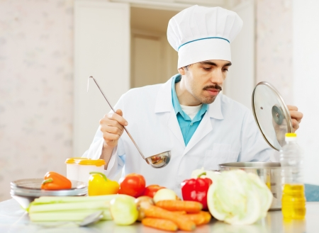 cook man works with vegetables  at kitchen photo