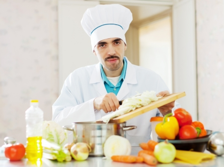 Handsome caucasian cook does veggie lunch at kitchen photo