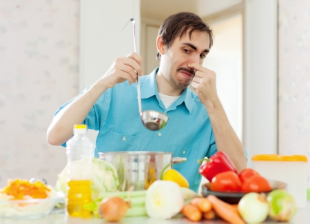 man holding her nose because of bad smell from pan  at home Stock Photo - 22109646