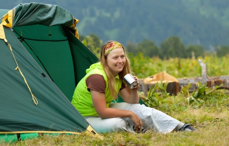 Happy female tourist drinking tea in front camp tent photo