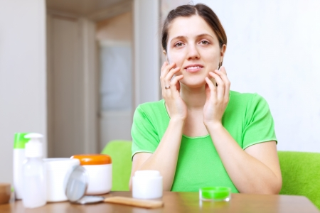 smiing: Smiing young woman uses cosmetic cream in home interior Stock Photo
