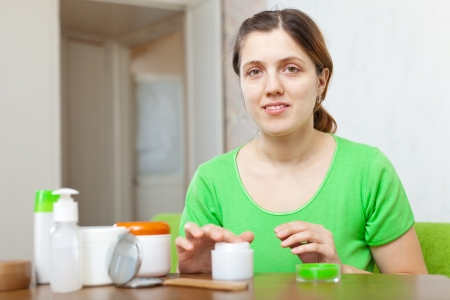 woman  in green caring for face with cream at home  photo