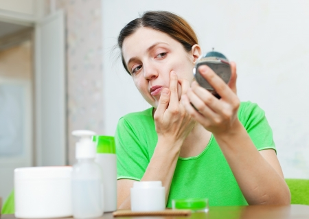 european young woman stares on her face in mirror at home photo
