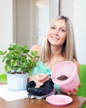 Girl works with  flower pots at her home photo