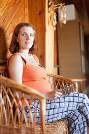 gravida: pregnant woman reading e-book in home interior