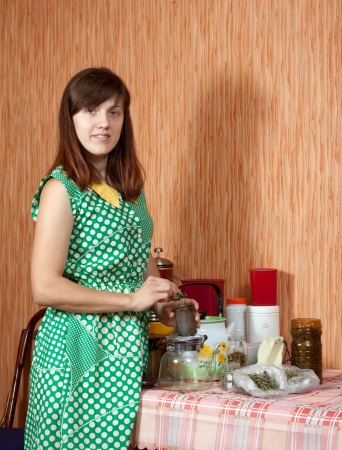 Woman brews herbs in a teapot at home kitchen photo