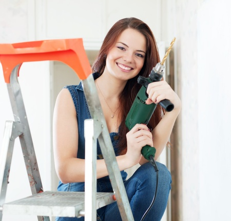 Happy girl in dungarees with drill on stepladder photo
