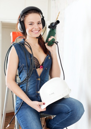 smiling sexy  girl in headphones with drill and hardhat on stepladder in interior photo