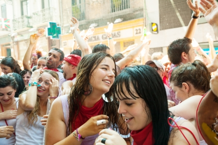 PAMPLONA, SPAIN - JULY 6: Cheering people at San Fermin feast in July 6, 2013 in Pamplona, Spain. Joyful youngsters are being sprayed with cold water