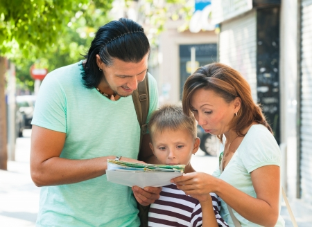 couple with teenage boy looking at the map during holiday photo