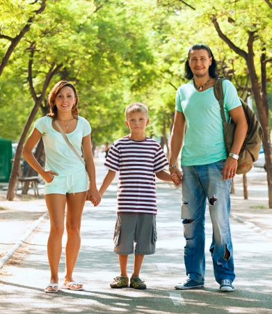 Happy family of three with teenager child in summer street photo
