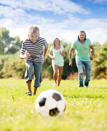 teenager boy with parents playing with soccer ball at summer park photo