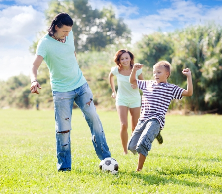 futbol soccer:  family with teenager child  playing with soccer ball at summer park