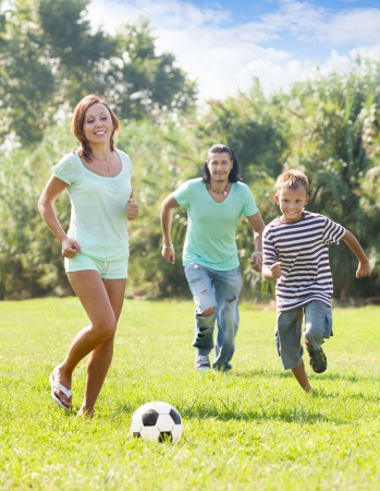 Happy parents with teenager son playing with soccer ball at summer park photo