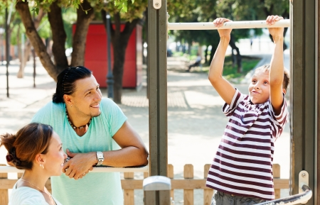 Happy parents with teenager training on pull-up bar at playground   photo