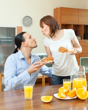 Woman serves croissants and scrambled eggs her beloved man in morning breakfast   photo