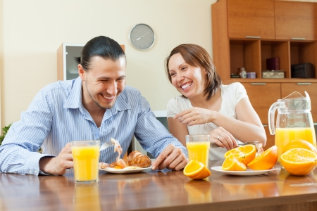 bacon portrait: Happy adult couple having breakfast with juice in morning at home interior  Focus on woman