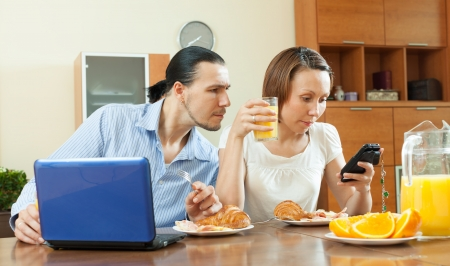 Couple using devices during breakfast time at home photo