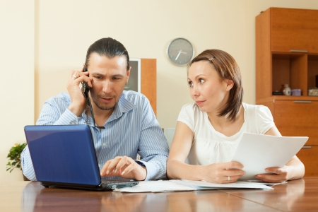 serious middle-aged man and woman looking financial document  photo