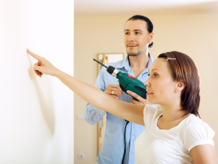 Сouple choosing point for hole in the wall at home photo