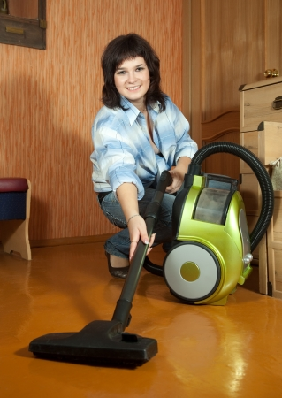 Woman cleaning with vacuum cleaner in living room photo