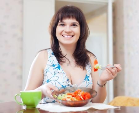 woman eats vegetarian salad at home photo