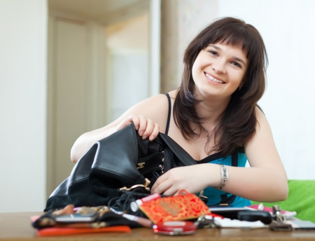Ordinary positive woman can not finding anything in her handbag at table  photo