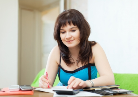 utility payments: serious housewife fills in  utility payments bills at  home