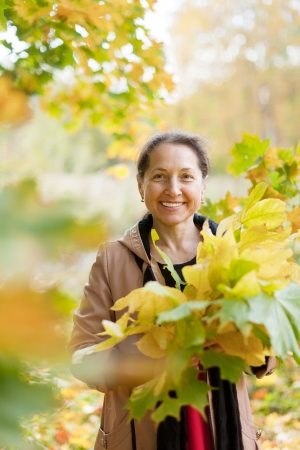 Outdoor portrait of  happy mature woman with maple posy Stock Photo - 22225541