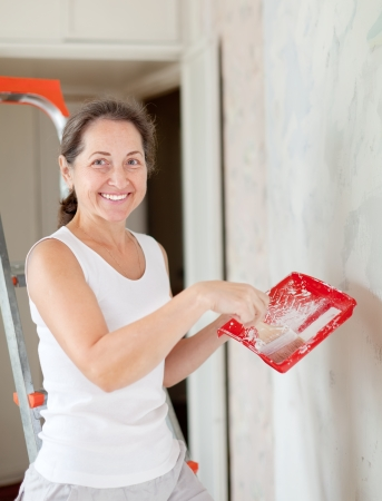 Happy mature woman paints wall with brush at home photo