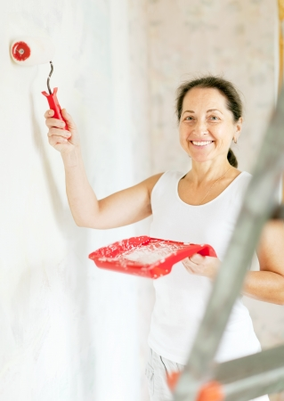 Happy woman paints wall with roller at home photo