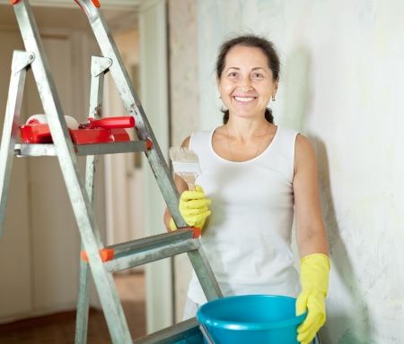 Mature woman makes repairs in the apartment photo