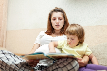 pregnant woman and child reads  book. Focus on mother photo