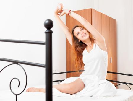awaking: Cheerful woman awaking on white sheet in  bed at home