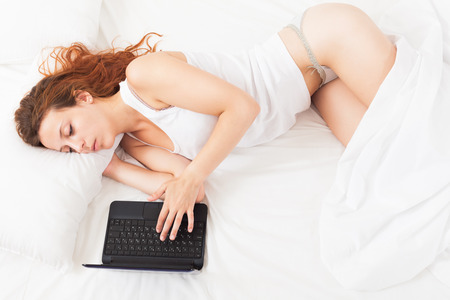 Sleepy young woman with laptop lying in her bed  photo