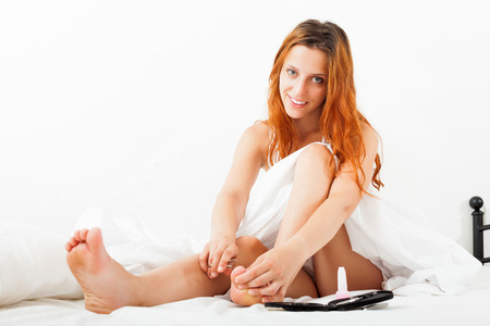 Beautiful red-haired girl cares for toenails with scissors in bed  photo