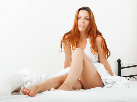 arouse: Long-haired funny woman lying on white sheets on the bed at home