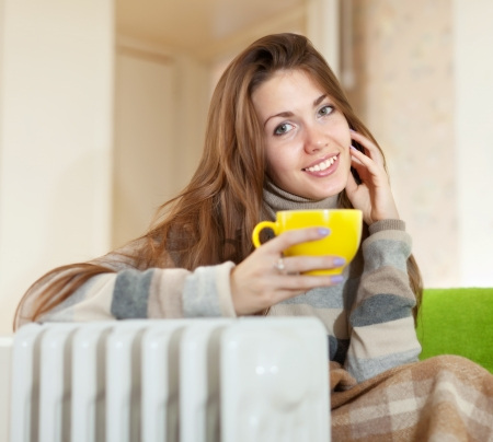 smiling woman  with yellow cup near oil heater at home