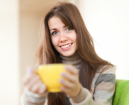 casualy: Smiling woman with yellow cup in home Stock Photo