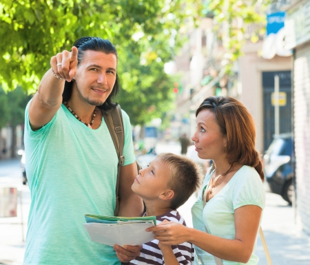 Middle-aged man pointing the direction for family at city street photo