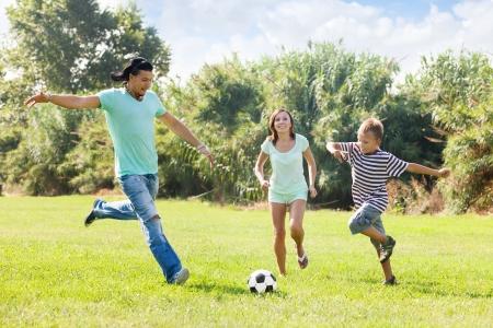 Familia de tres con adolescente que juega en el f�tbol photo
