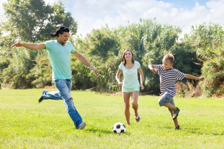 women playing soccer: Family of three with teenager playing in soccer Stock Photo