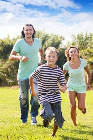Happy sporty family of three running on grass at park photo