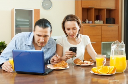 electronic devices: Happy couple using electronic devices during breakfast time  Stock Photo